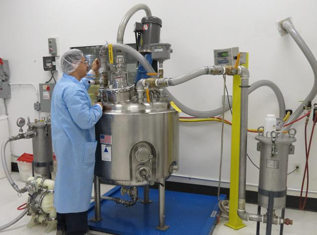 scientist next to large aluminum tank